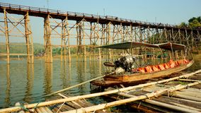 Long-tail boat and the wooden bridge over Song Karia river. The long-tail and the longest wooden bridge in Thailand was constructed by Mon people to cross Song royalty free stock photography