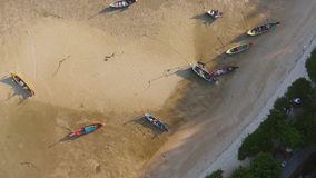 Long-tail boats in low water during low tide on the Rawai beach at Phuket Island, Thailand. HD top aerial view. stock footage