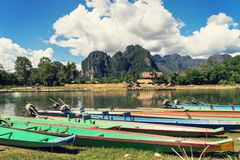 Long tail boats on sunset at Song river, Vang Vieng, Laos. Long tail boats on sunset at Song river, Vang Vieng, Laos royalty free stock photography