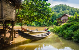 Long-tail boats in a village of stilt houses, Thailand. Long-tail boats moored in a village of stilt houses Royalty Free Stock Photography