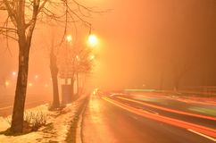 Long tail lights traces on misty night road. Long traces of tail lights of passing cars in foggy orange atmosphere colored by street lamps. Long exposure stock images