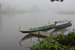 Long tail motor boat mooring near quayside with morning mist Stock Photos
