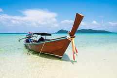 Long tail wooden boat anchor with csytal sea white sand Royalty Free Stock Photo