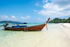 Long tail wooden boat anchor with csytal sea white sand Stock Photo