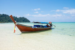 Long tail wooden boat anchor with csytal sea white sand Royalty Free Stock Image