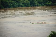 A long-tailed boat with full passengers is running upstream agai. Nst the river tide along muddy of Mekong river at Amphoe Khong Chiam, the easternmost district Stock Image