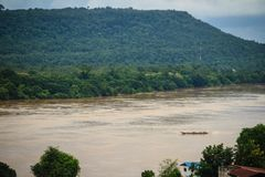 A long-tailed boat with full passengers is running upstream agai. Nst the river tide along muddy of Mekong river at Amphoe Khong Chiam, the easternmost district Royalty Free Stock Image