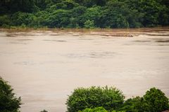 A long-tailed boat with full passengers is running upstream agai. Nst the river tide along muddy of Mekong river at Amphoe Khong Chiam, the easternmost district Royalty Free Stock Images