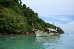 Long-tailed boat on tropical ocean near the hill Stock Images