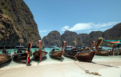 Long-tailed boats, Koh Phi Phi,Thailand. Colorfully decorated long-tail boats in turquoise water against a background of karst mountains at scenic Maya Bay, Koh Royalty Free Stock Image