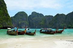 Long-tailed boats on Maya beach. Maya beach, Thailand - September 1, 2014: Long tailed boats and unidentified people on Maya beach, an island of the Phi Phi royalty free stock image