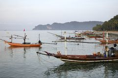 Long-tails boats in Thailand. Long-tails boats at sunrise on the beach of Chumphon - Thailand Royalty Free Stock Images