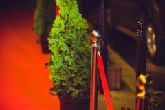 Long tapis rouge entre les barrières de corde sur l'entrée image stock