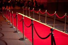 Long tapis rouge entre les barrières de corde sur l'entrée photos stock