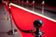 Long tapis rouge entre les barrières de corde sur l'entrée photographie stock