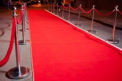 Long tapis rouge entre les barrières de corde sur l'entrée photographie stock libre de droits