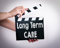Long term care concept. Female hands holding movie clapper.  Stock Photo