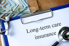Long-term care insurance form. Long-term care insurance form and dollars Royalty Free Stock Photo