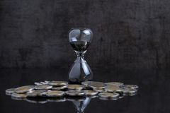 Long term investment or financial time counting down concept, sa. Ndglass / hourglass with coins on black table and black cement loft background Royalty Free Stock Image