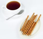 Long thin biscuit sticks tea. Long thin biscuit sticks and a cup of tea Royalty Free Stock Image