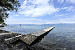 A long and a thin dock in the shore of Lake Ohrid. Clouds in the sky on a sunny day. A shadow of a tree is laid over the beginning of the dock, and the Sun is Stock Photos