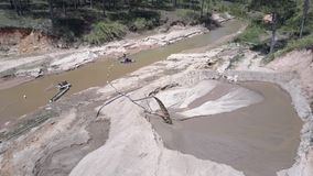 Long thin pipe extracts wet sand from narrow muddy river
