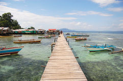 Long timber pier and boats. Jayapura, Indonesia Royalty Free Stock Image