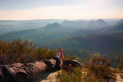 Long tired male legs in dark  hiking trousers take a rest on peak of rock above valley. Stock Images
