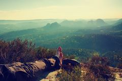 Long tired male legs in dark  hiking trousers take a rest on peak of rock above valley. Stock Photo