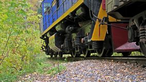 Long train running fast on railway on beautiful autumn forest. Slow motion. 3840x2160. Long train with carriage running fast on railway on beautiful autumn stock video footage