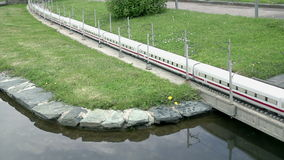 Long train passing the river. Model of extra long electric train driving through bridge over the river placed in Minimundus in Klagenfurt, Austria stock video
