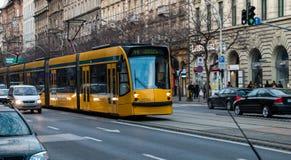 Long tram jaune sur des rues de Budapest Photographie stock libre de droits