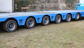 Long truck with six pairs of wheels for exceptional transport. Very long blue truck with six pairs of wheels for exceptional transport royalty free stock images