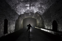 Man tunning from light. Long tunnel with light an man running away from it, silhouette Stock Photos
