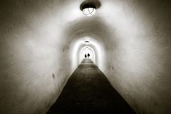 A long tunnel with white walls and arched ceiling. Two people ar royalty free stock images