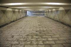 Long underground passage. The underground passage lined with gray granite and marble Stock Photography
