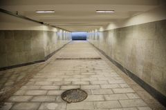 Long underground passage. The underground passage lined with gray granite and marble Stock Photo