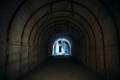 Long underground tunnel with light in end. Concrete corridor of abandoned bunker stock photos