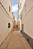 Long very narrow street. With vertical walls in the sun, and in the top you can see the blue sky and white clouds on the background Royalty Free Stock Images