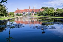Long view of the laboratory across the Jellicoe Canal at Wisley. Garden centre, Surrey, with water lilies and deep reflections in the foreground royalty free stock photos