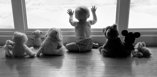 The long wait for spring. A baby sits at the window with stuffed animal friends waiting for winter to be over Stock Photography