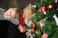The long wait. Young children waiting by the christmastree until they can open the presents Royalty Free Stock Photos