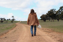 The long walk. Image of a man walking along a dirt road. By the looks of it, he has a long way to walk Stock Photography