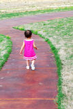 This Is a Long Walk. A little girl walking down a sidewalk dressed in a pretty pink dress and sandels Stock Image