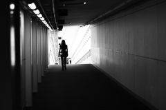 Long walk to the plane. Girl walking down a long airport terminal hallway Stock Photography