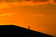 The long walk to the summit. Silhouette of person walking to the top of a hill, at sunset Royalty Free Stock Images