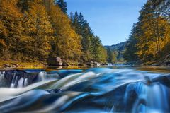 Long waterfall and river with rocks high in the mountains. Autumn mountains landscape. Idea for outdoor activities, travel. Long waterfall and river with rocks stock photography
