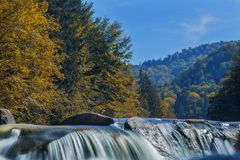 Long waterfall and river with rocks high in the mountains. Autumn mountains landscape. Idea for outdoor activities, travel. Long waterfall and river with rocks stock photo