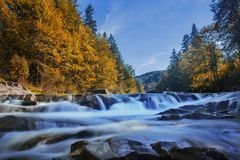 Long waterfall and river with rocks high in the mountains. Autumn mountains landscape. Idea for outdoor activities, travel. Long waterfall and river with rocks royalty free stock image