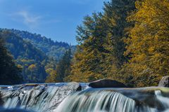 Long waterfall and river with rocks high in the mountains. Autumn mountains landscape. Idea for outdoor activities, travel. Long waterfall and river with rocks royalty free stock photos